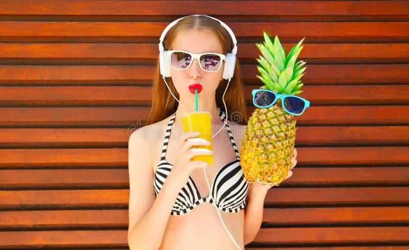 画象俏丽的微笑的妇女用滑稽的菠萝和果汁杯子在耳机 库存照片