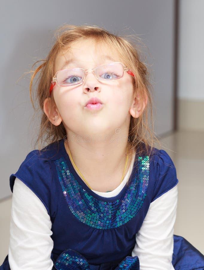 画象做滑稽的面孔的小女孩孩子做乐趣 免版税库存照片