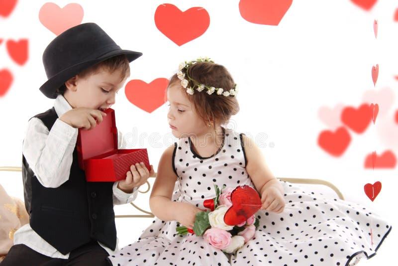象分享礼物的女孩和绅士男孩的夫人 库存照片