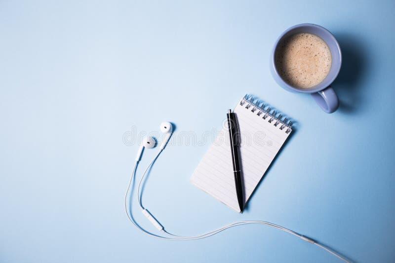 象办公室汤用品的夹子 在被打开的笔记本、笔、耳机、膝上型计算机和咖啡的顶视图在蓝色的 免版税库存图片