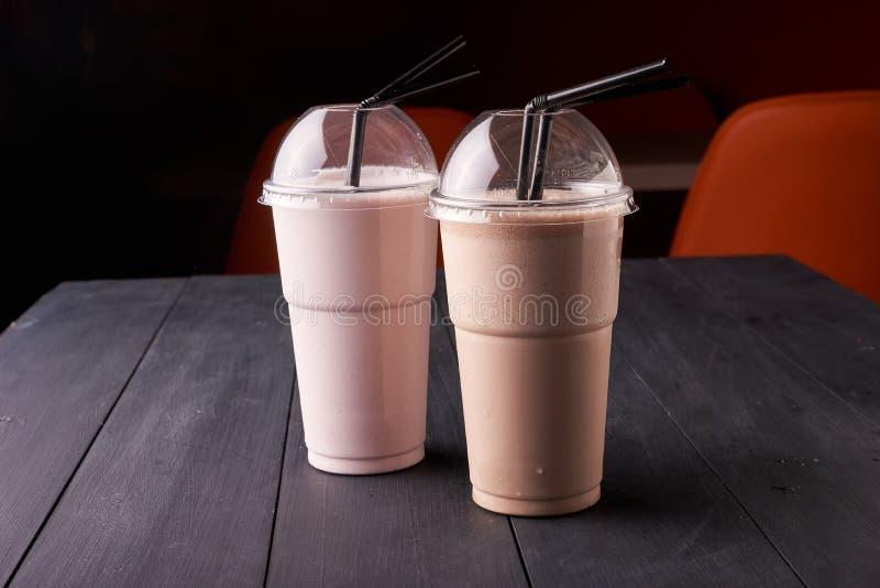 象圆滑的人或奶昔的健康和鲜美水果鸡尾酒在塑料杯子 免版税库存照片