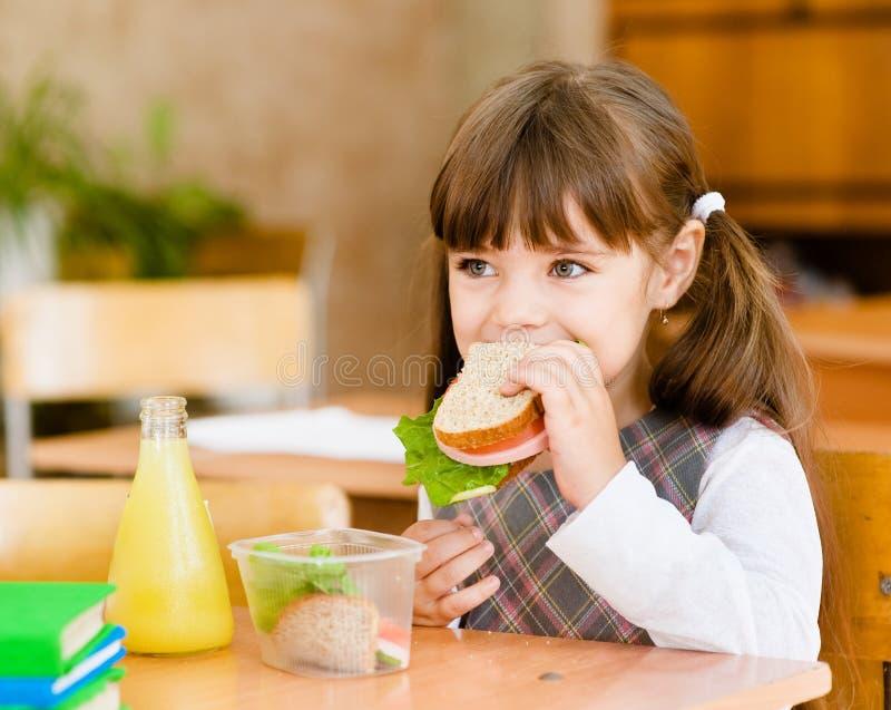 画象女小学生,当吃午餐在期间时 免版税库存照片
