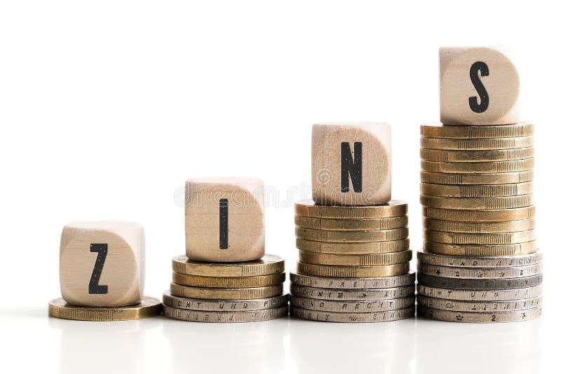象征被堆积的硬币提高与词`的利率感兴趣`用德语 免版税库存图片