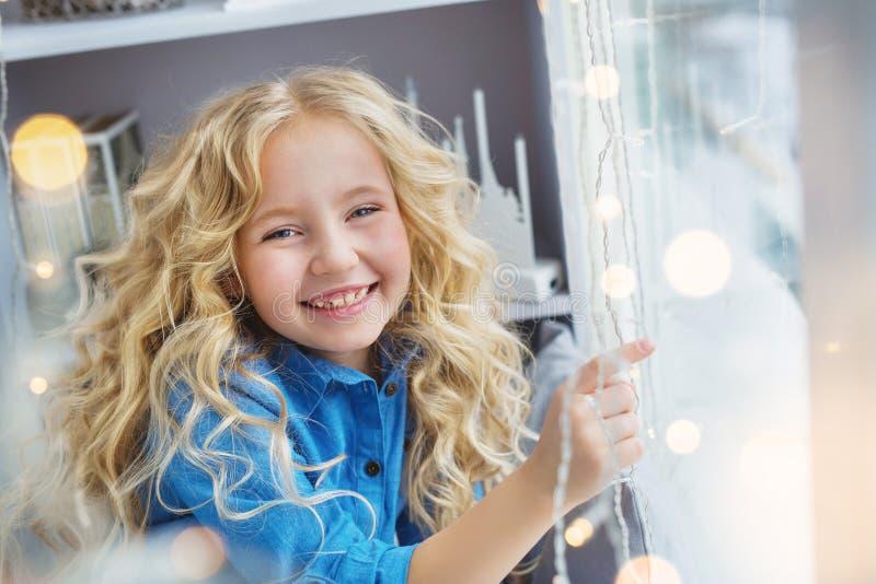 画象微笑相当小女孩坐窗台 免版税库存图片