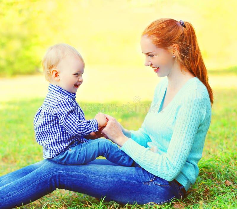 画象愉快的微笑的母亲和儿子孩子户外在晴朗的公园 免版税库存图片