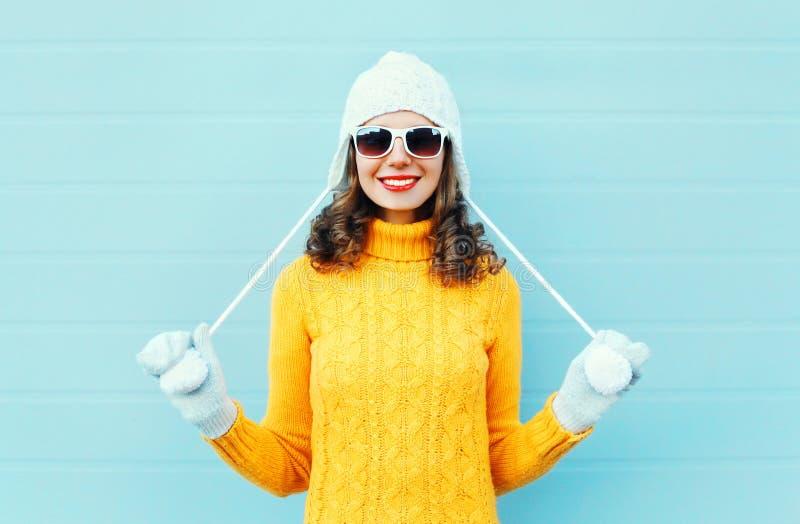 画象愉快年轻微笑的妇女佩带太阳镜,被编织的帽子,在蓝色的毛线衣 免版税库存照片
