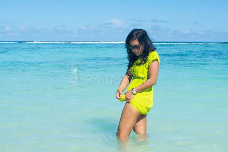画象接近站立在海洋和修理她的礼服的年轻美丽的亚裔女孩 图库摄影