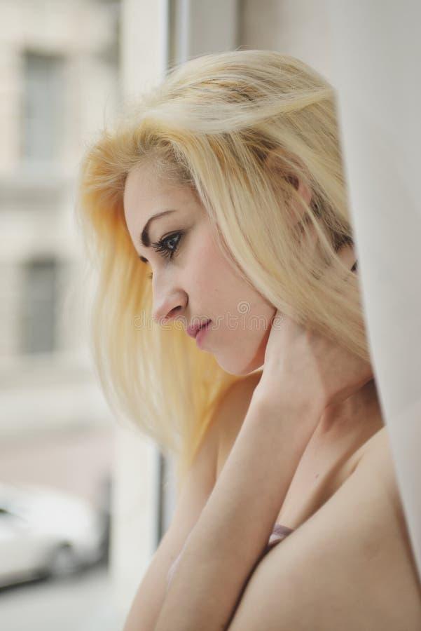 画象接近年轻美丽的白肤金发的妇女在窗口附近 免版税图库摄影