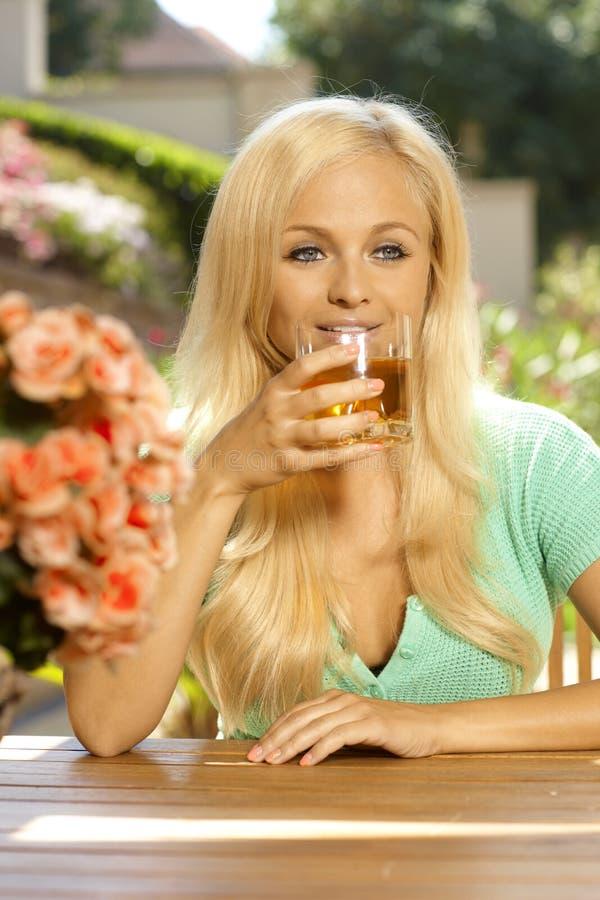 画象有吸引力年轻白肤金发妇女喝 免版税库存照片
