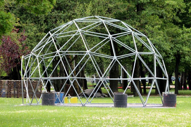 象框架的金属圆顶与入口和桶重量在密集地方的公园离开在音乐会以后被包围与未割减的草和 免版税图库摄影