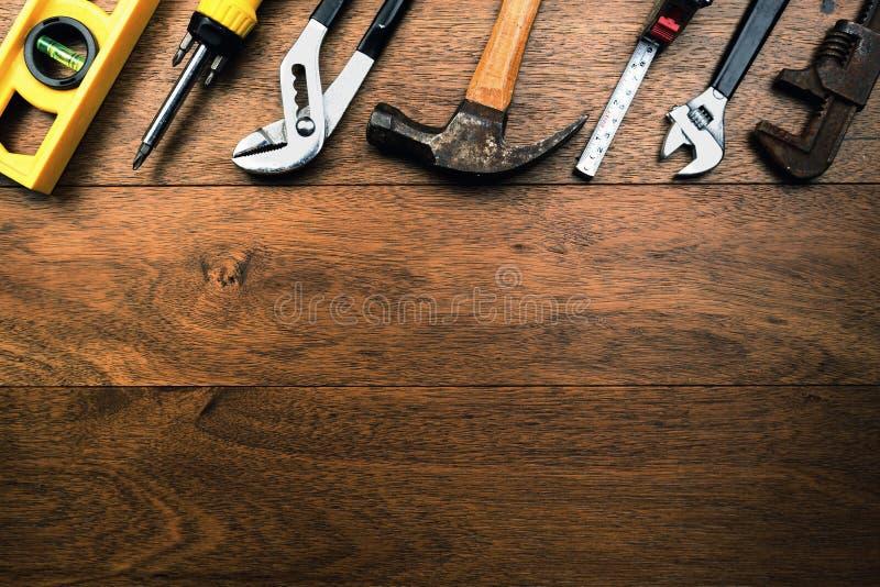 象水标度、钳子、螺丝刀、锤子和卷尺的脏的生锈的工匠工具在与室的木板条为写 库存照片