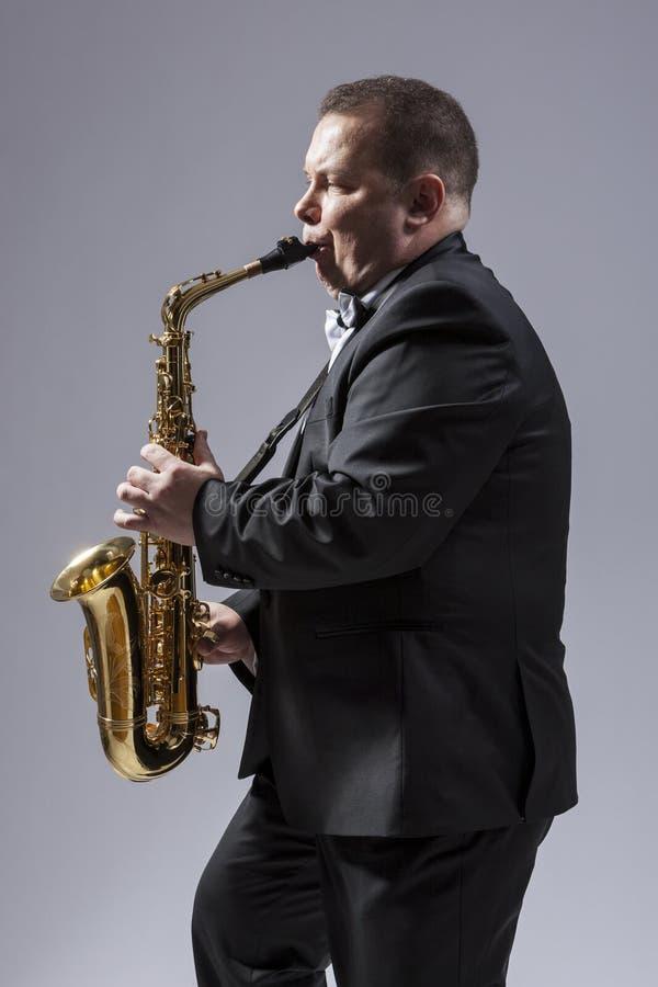 画象白种人成熟被集中的萨克管演奏员 免版税库存图片