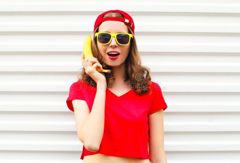 画象相当凉快的妇女用获得的香蕉在白色的乐趣 库存图片