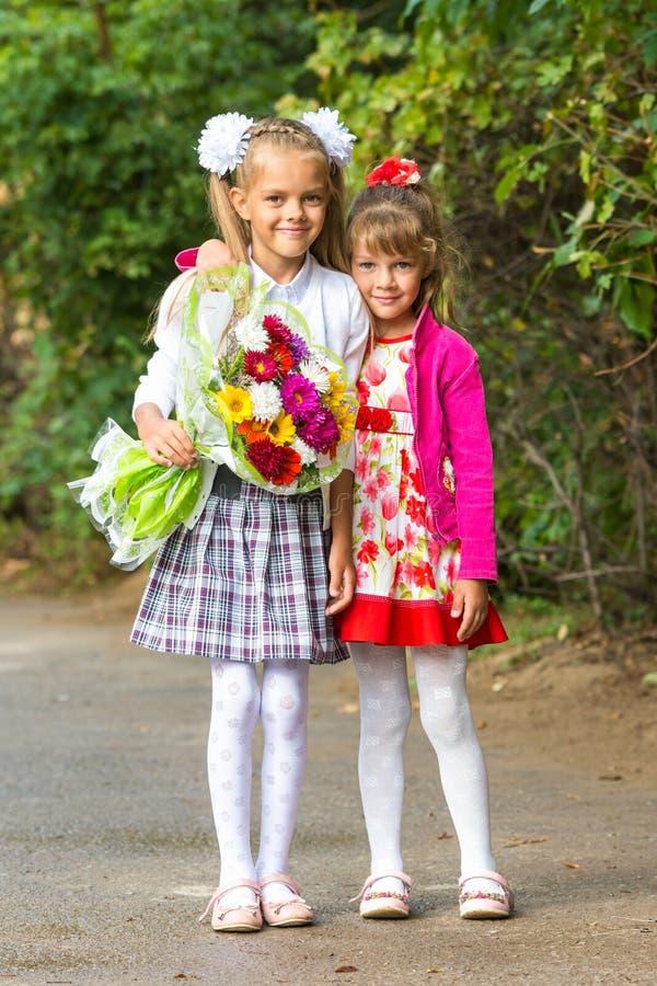 画象第一辆平地机和她的妹妹在途中对学校 免版税图库摄影