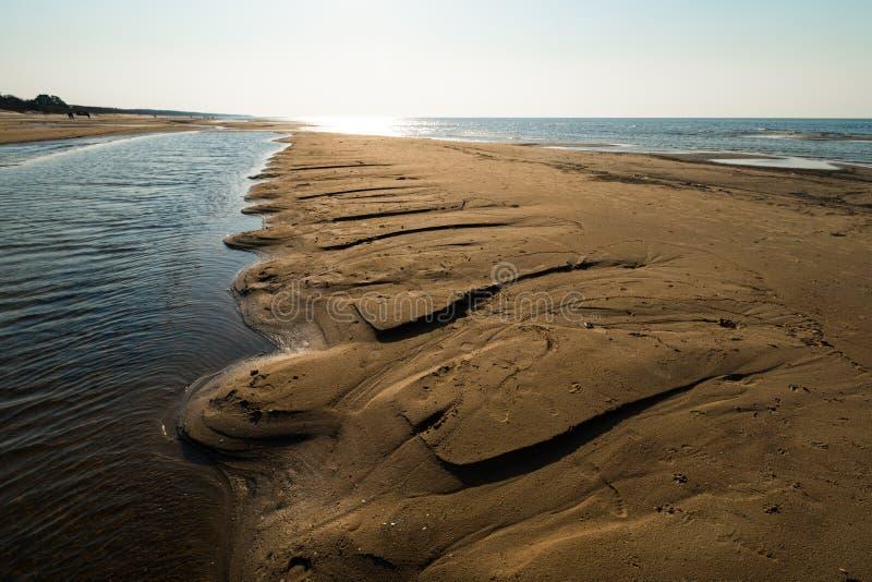 象织地不很细沙子-波罗的海与白色沙子的海湾海滩的点心在日落 免版税库存图片