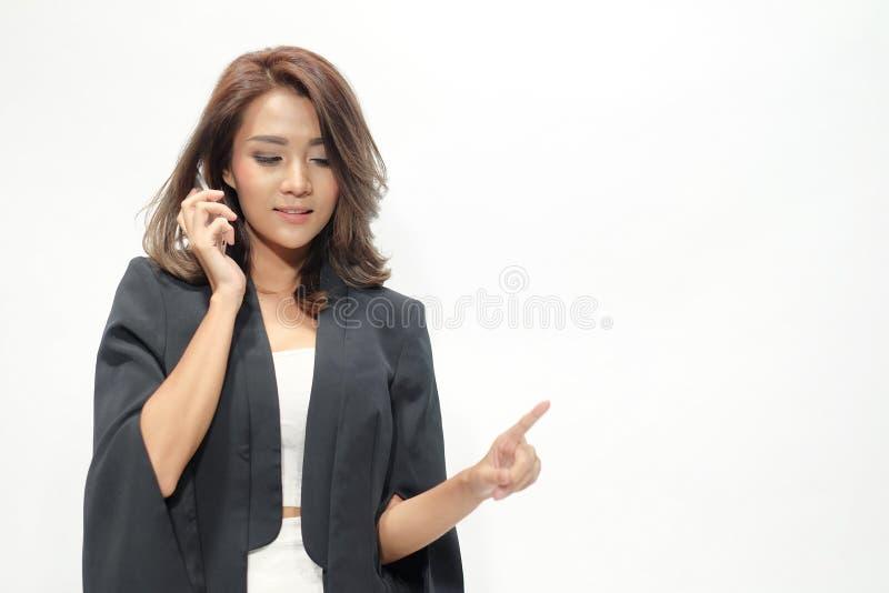 画象美好的亚洲妇女身分,拿着电话, 免版税库存照片