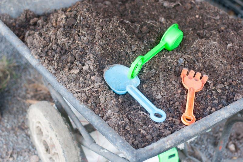 象耙和铁锹的塑料农业工具在金属推车的黑土壤投入了准备好对使用为孩子学会 库存照片