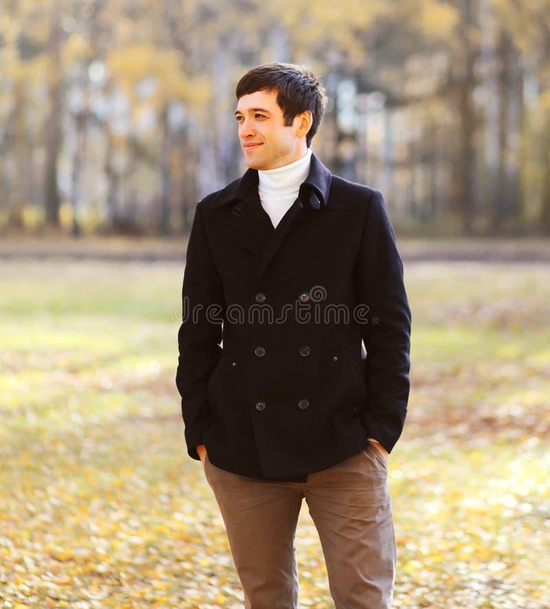 画象英俊的微笑的人在晴朗的秋天的穿黑外套夹克 免版税库存照片
