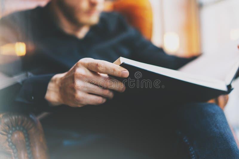 画象英俊的有胡子的人佩带的玻璃染黑衬衣 供以人员坐在葡萄酒椅子大学图书馆、阅读书和relaxi里 免版税图库摄影