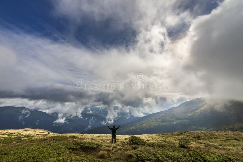 象草的小山的人与在多云天空蔚蓝和绿色木质的山背景的被举的胳膊 库存图片