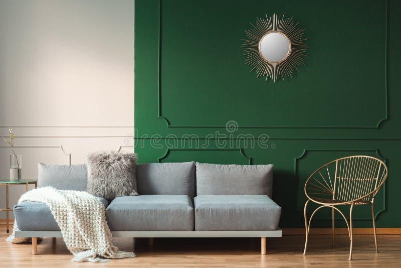象镜子的太阳形状在客厅内部绿色墙壁上与斯堪的纳维亚沙发的有枕头的 免版税库存图片