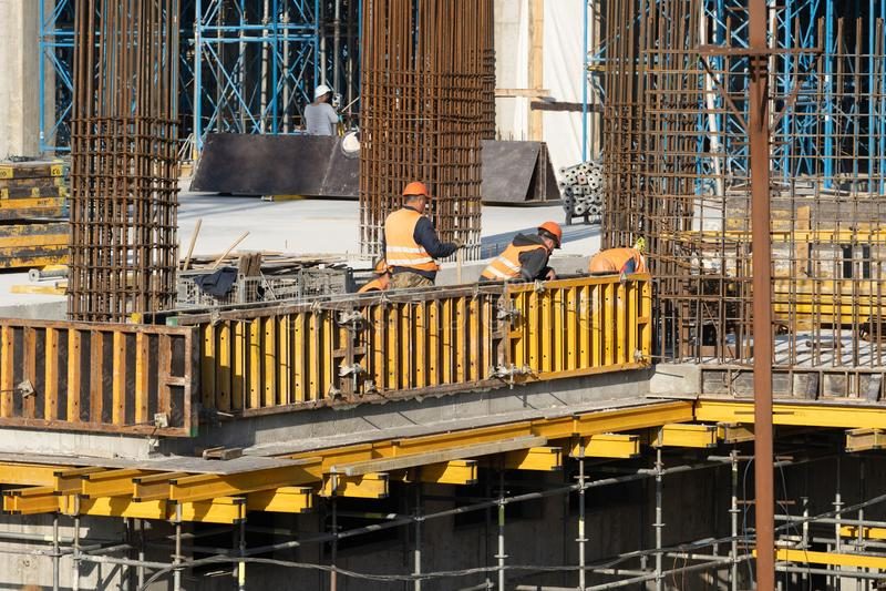 象队的多层的高层建筑物建筑的工作者 库存图片