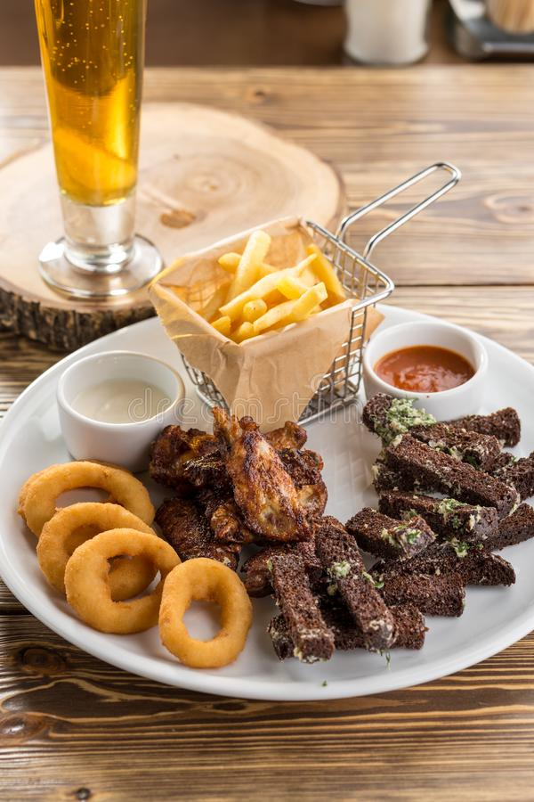 象鸡翅、薯条、黑麦面包油煎方型小面包片和杯的被分类的快餐在木桌上的啤酒 免版税库存图片