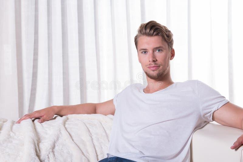 画象年轻人坐长沙发 免版税库存照片