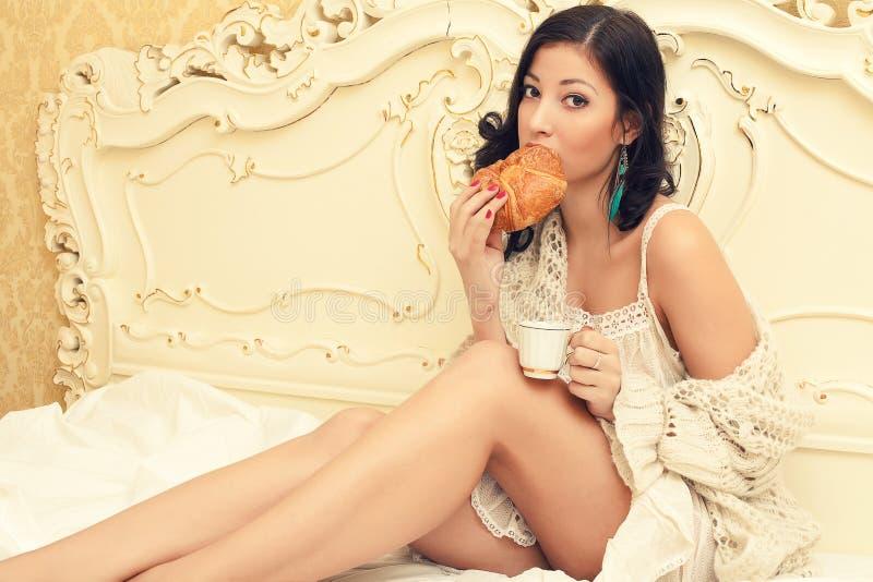 画象年轻美丽深色食用早餐 免版税库存照片