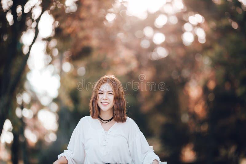 画象年轻行家亚洲女孩笑和微笑摆在autume公园森林背景中 免版税库存照片