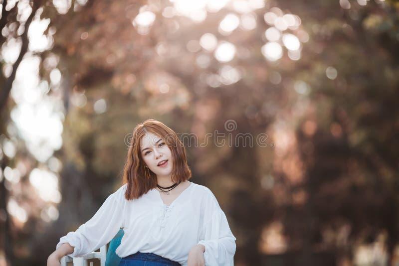画象年轻行家微笑亚洲女孩摆在厚颜无耻在秋天公园森林bokeh背景中 库存图片