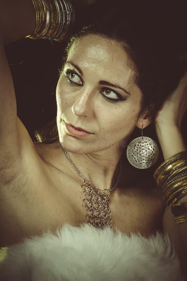 豪华、深色的妇女佩带的白色毛皮和金首饰 库存照片