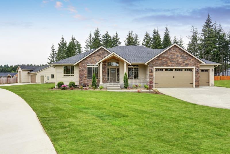豪华一平实房子外部与砖修剪和车库 免版税库存图片