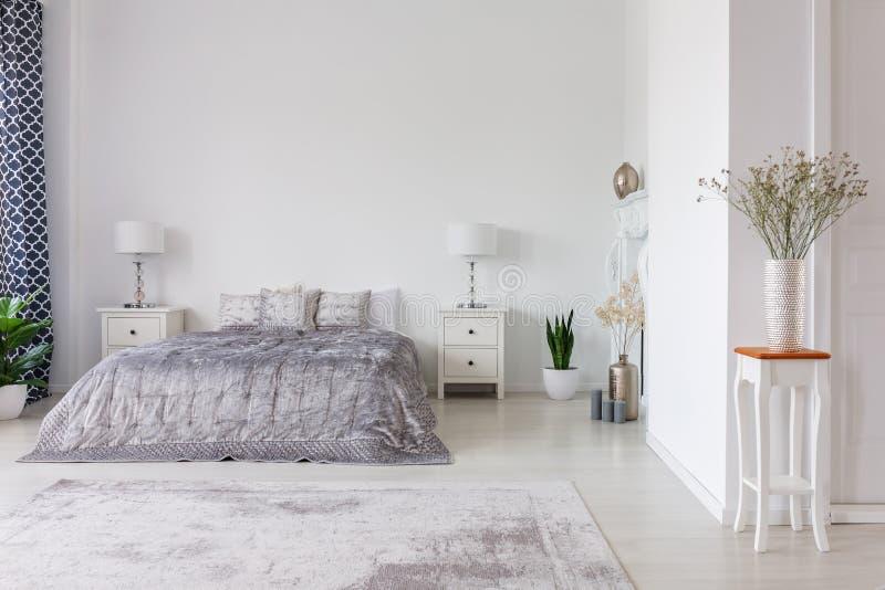 豪华与银色鸭绒垫子和枕头的卧室室内设计在亲切的大小床,与拷贝空间的真正的照片上 库存图片