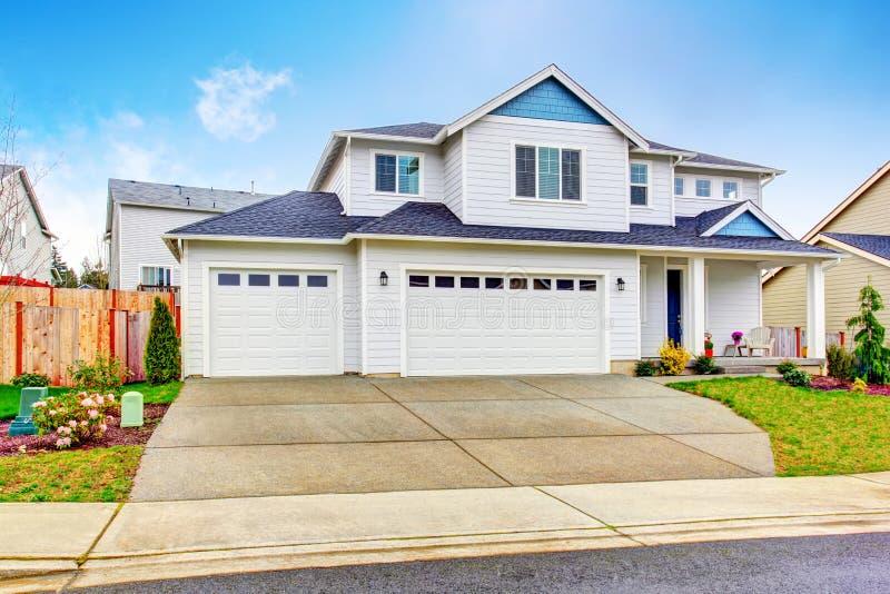 豪华两层的房子外部与车库和具体车道 免版税库存图片