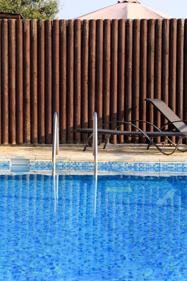 豪华假日别墅游泳场设计现代建筑学  在有扶手栏杆的,轻便折叠躺椅,太阳异乎寻常的游泳场附近放松 免版税库存图片