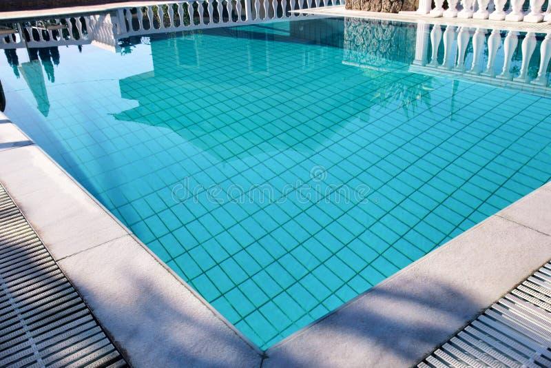 豪华假日别墅游泳场设计现代建筑学  在有扶手栏杆的,轻便折叠躺椅,太阳异乎寻常的游泳场附近放松 库存照片