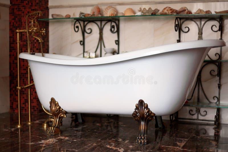 豪华在精妙的内部的葡萄酒古铜色clawfoot独立bathtube 与壳的黑暗的温暖的颜色背景在架子 免版税图库摄影