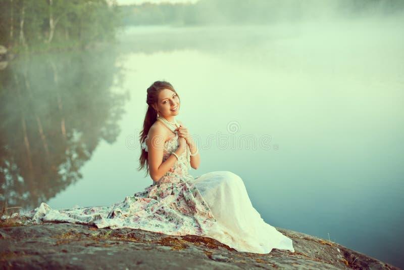 豪华妇女在一件长的葡萄酒礼服的一个森林里在湖附近 免版税库存图片