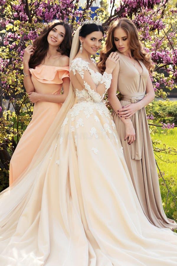 豪华婚礼礼服的华美的新娘,摆在与庄重装束的美丽的女傧相 免版税库存图片