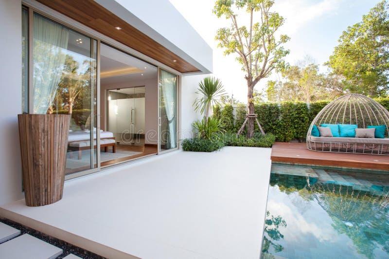豪华室内设计在水池别墅卧室与舒适床的与在房子或住宅建设的高被提高的天花板 库存照片