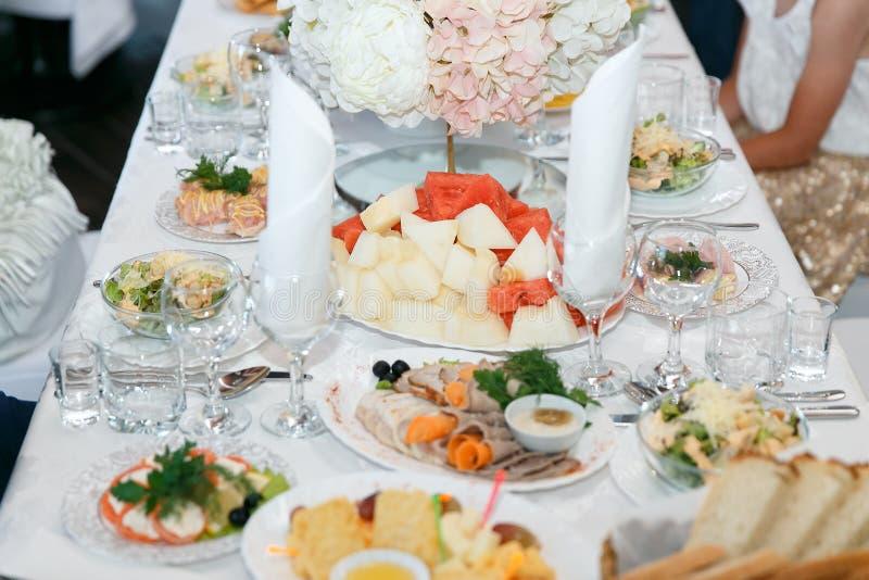 豪华宴会桌设置在餐馆 与葡萄酒杯、快餐和鸡尾酒的表 库存图片