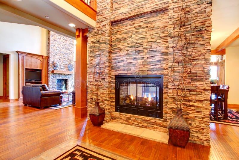豪华房子内部。有壁炉的石墙 免版税库存图片