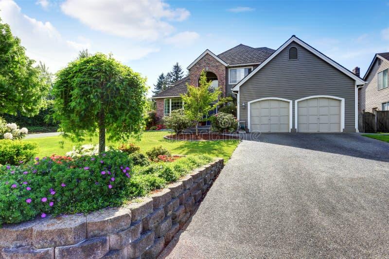 豪华房子外部与砖和房屋板壁修剪和双重车库 库存图片