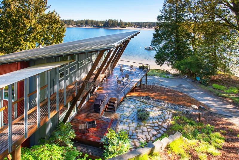 豪华房子大被盖的和用装备的门廊有湖的看法 免版税库存照片