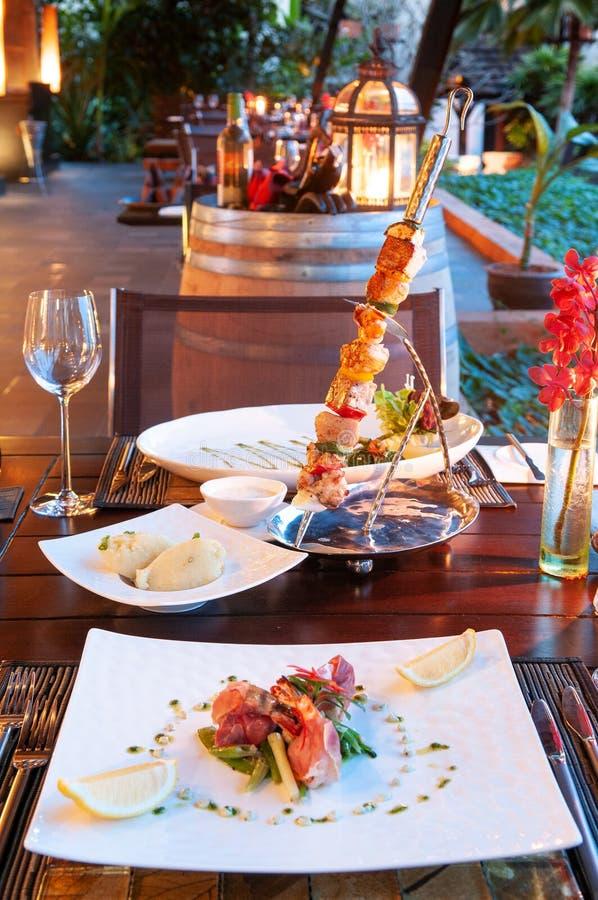 豪华旅游胜地餐馆与烤肉的饭桌设置和 免版税库存照片