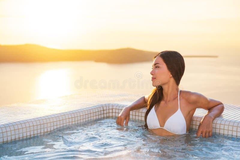 豪华旅馆旅行妇女在温泉水池旅馆里有陆间海背景 圣托里尼假期夏天休假女孩享用 库存图片