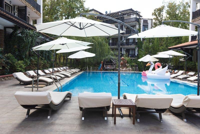 ?? 豪华旅馆的游泳场有伞和椅子的 旅馆手段在保加利亚,旅行的普里莫尔斯克 库存照片