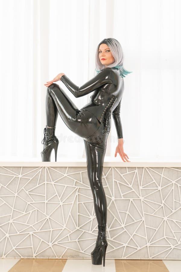 豪华时尚女孩,打扮在一套黑乳汁橡胶猫衣服,站立在单独白色窗口背景  免版税图库摄影