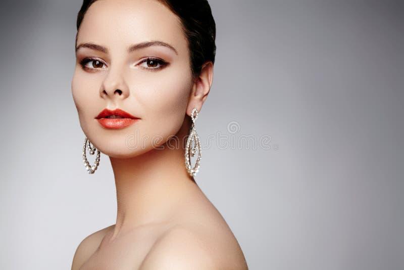豪华时尚耳环的美丽的愉快的妇女 与brilliants的金刚石发光的首饰 性感的减速火箭的样式画象 免版税图库摄影
